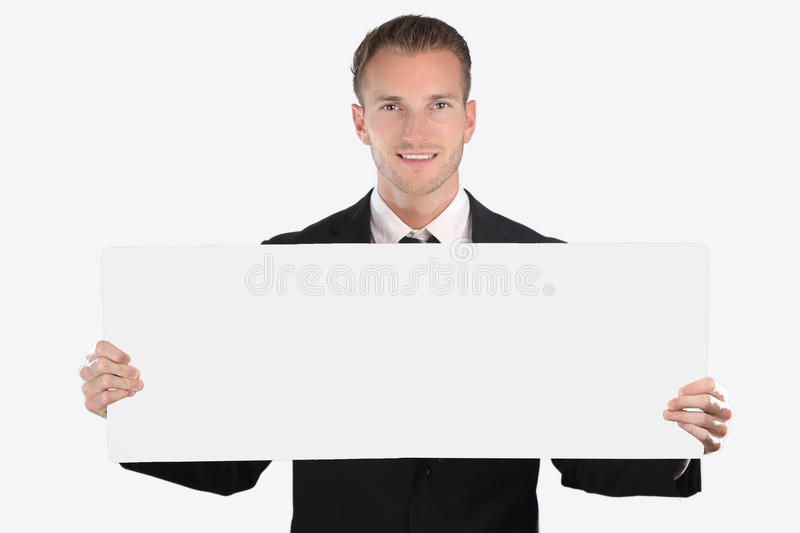 Cheerful young businessman showing blank signboard. On a white background royalty free stock photos