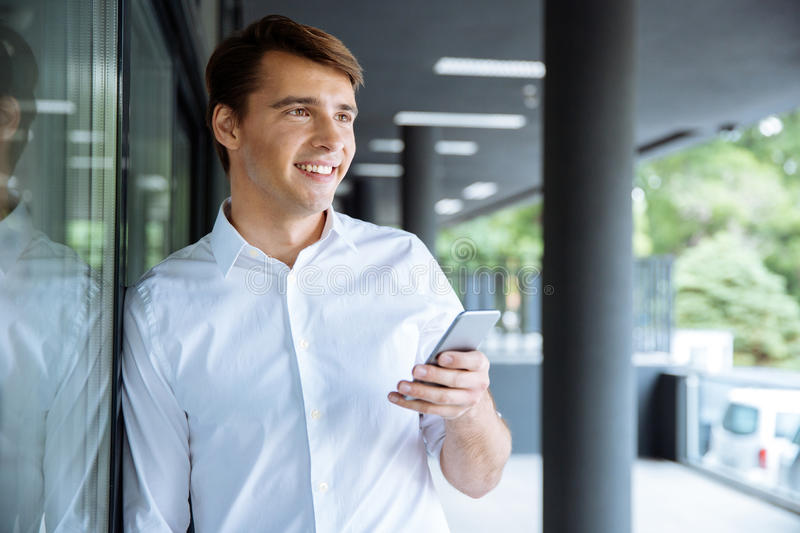 Cheerful young businessman using cell phone royalty free stock photography