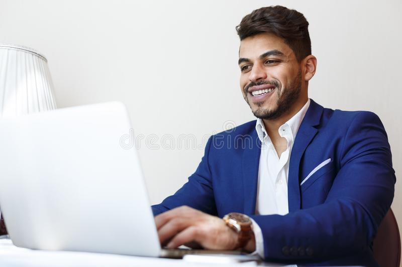 Cheerful young businessman working with laptop in hotel room royalty free stock photography