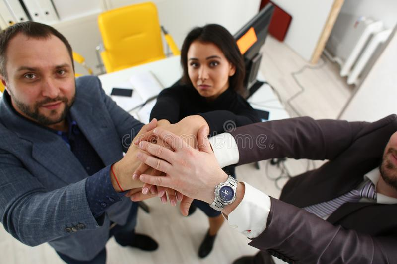 Portrait of cheerful young businessmen in office place their hands one over the other stock photo
