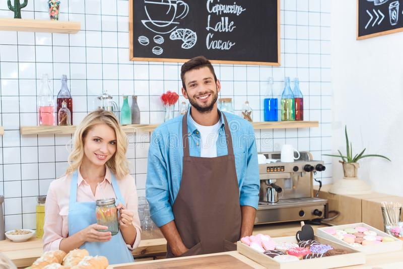 Cheerful young cafe workers in aprons smiling. At camera royalty free stock photography