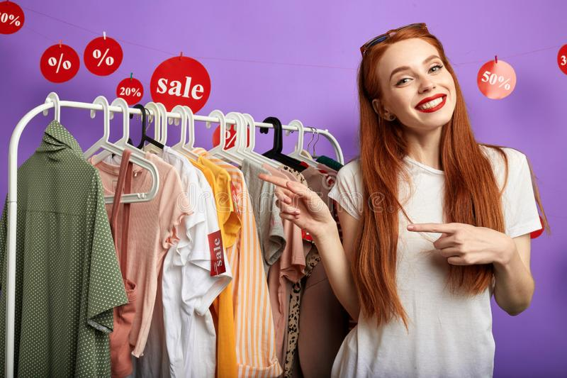 Cheerful young charming girl pointing to the clothes stock image