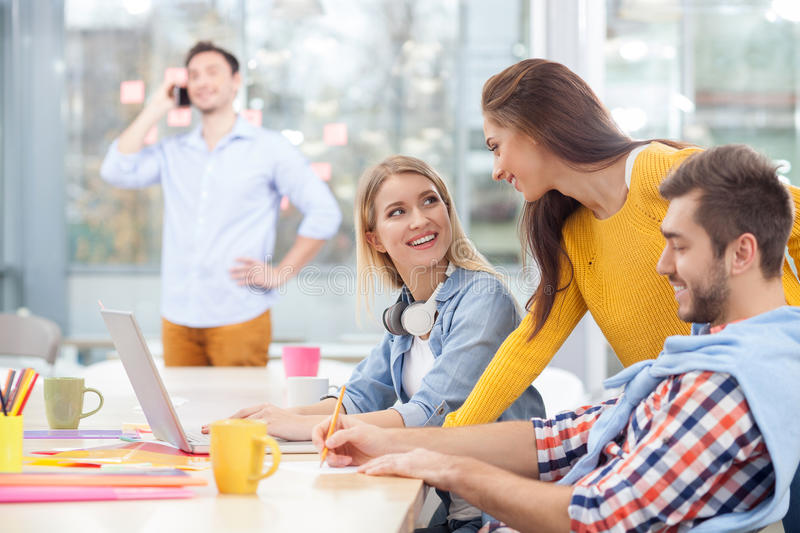 Cheerful young colleagues are discussing new royalty free stock photo