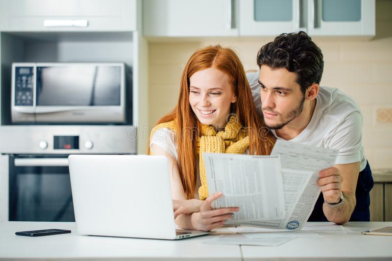 Cheerful young couple calculating their bills at home. Happy couple at home paying bills with laptop and looking screen royalty free stock images