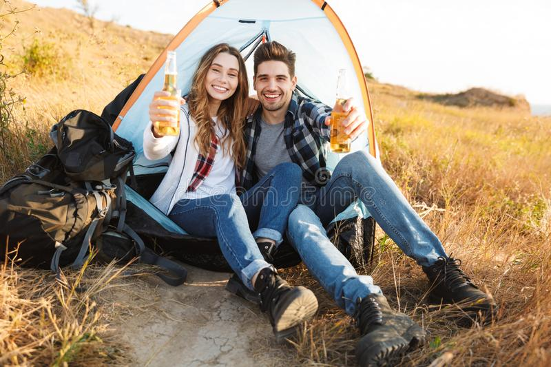 Cheerful young couple camping, sitting. At the tent, drinking beer royalty free stock images