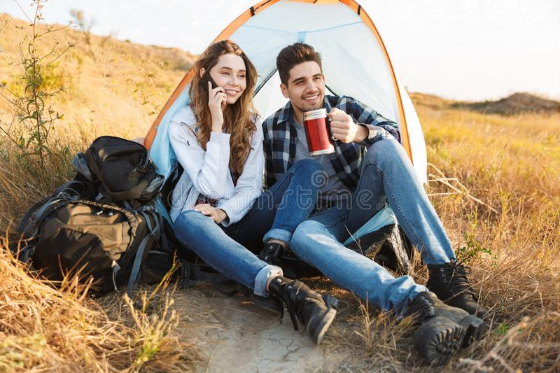 Cheerful young couple camping, sitting. At the tent, having a videocall royalty free stock photos