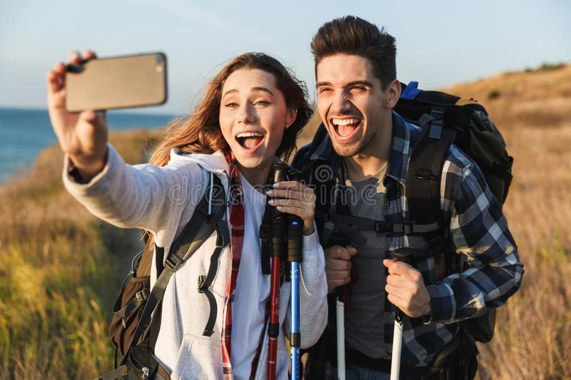 Cheerful young couple carrying backpacks hiking together. Walking on a trail, taking a selfie royalty free stock images