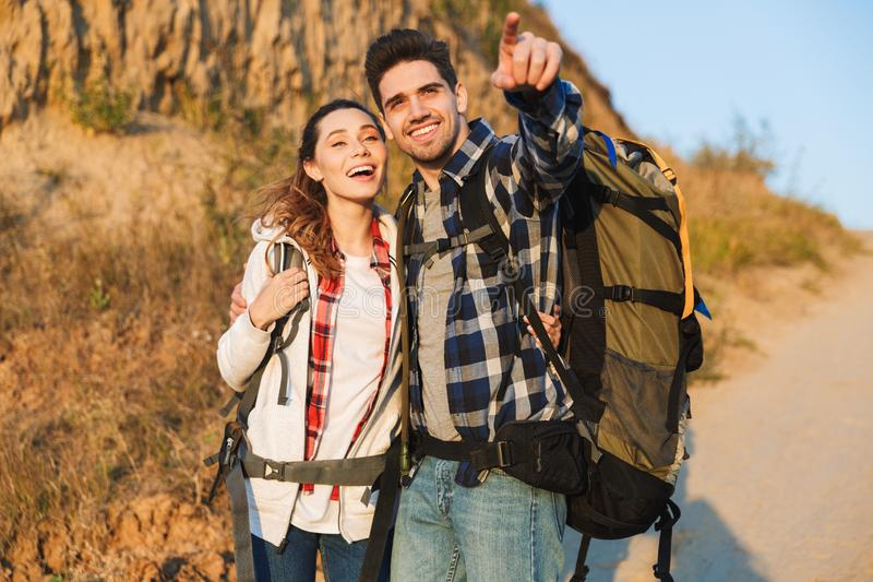 Cheerful young couple carrying backpacks hiking together. Walking on a trail, pointing finger stock image