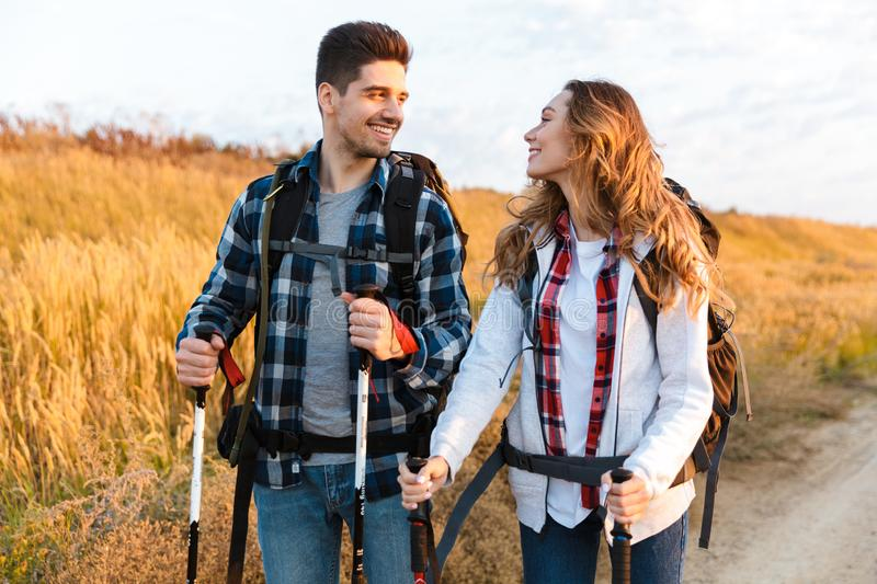 Cheerful young couple carrying backpacks hiking together. Walking on a trail royalty free stock photos