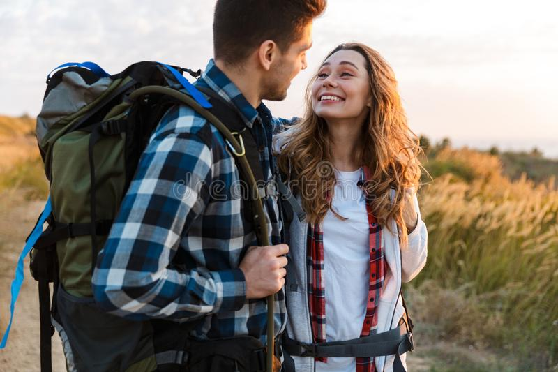 Cheerful young couple carrying backpacks hiking together. Walking on a trail stock photography