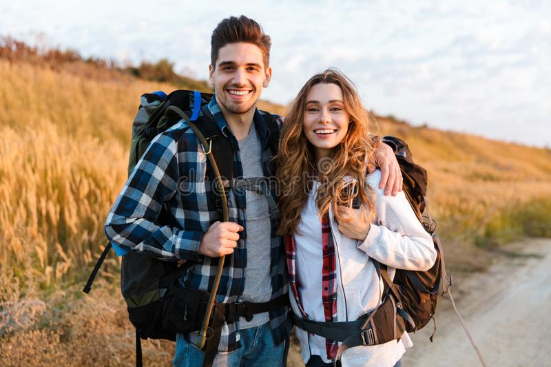 Cheerful young couple carrying backpacks hiking together. Walking on a trail royalty free stock photo