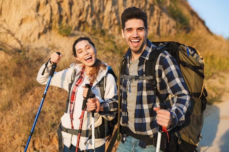 Cheerful young couple carrying backpacks hiking together. Walking on a trail royalty free stock images