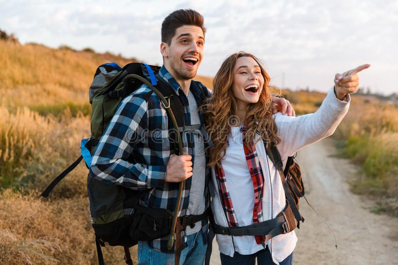 Cheerful young couple carrying backpacks hiking together. Walking on a trail stock photos