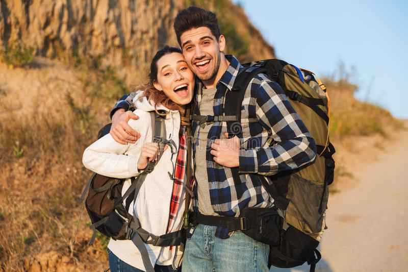 Cheerful young couple carrying backpacks hiking together. Walking on a trail, hugging royalty free stock images