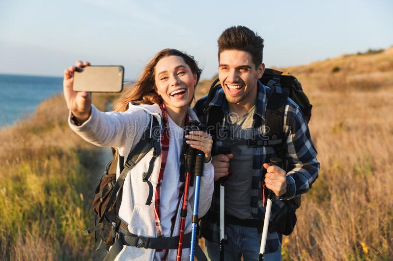 Cheerful young couple carrying backpacks hiking together. Walking on a trail, taking a selfie stock photo