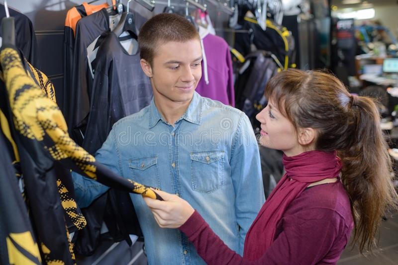 Cheerful young couple choosing items in sport clothes shop royalty free stock photos