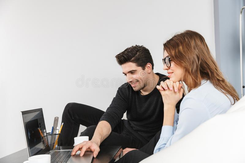 Cheerful young couple of colleagues working together royalty free stock photos