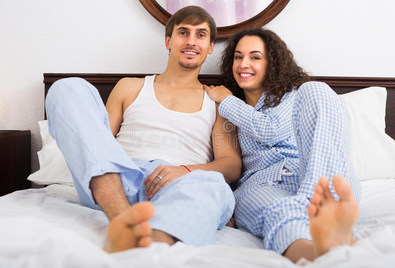Cheerful young couple in family bed. Cheerful young couple in sleepwear relaxing in family bed stock image