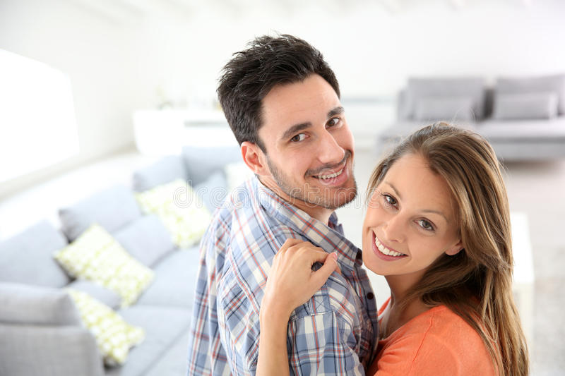 Cheerful young couple at home living-room. Cheerful young loving couple at home royalty free stock photos