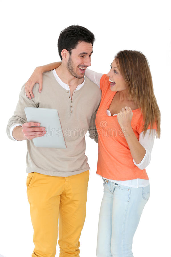 Cheerful young couple isolated with tablet. Cheerful couple using digital tablet, isolated stock image