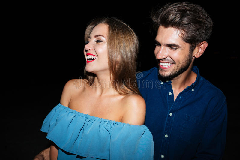 Cheerful young couple laughing together at night royalty free stock image