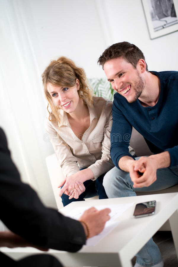 Cheerful young couple with salesman agent at home royalty free stock image