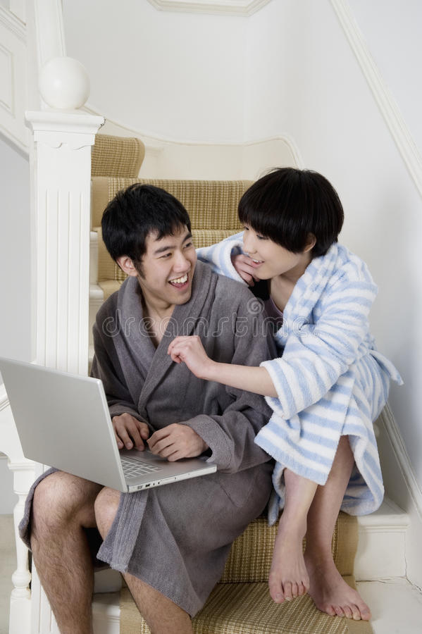 Cheerful young couple sitting on stairway using laptop stock photo
