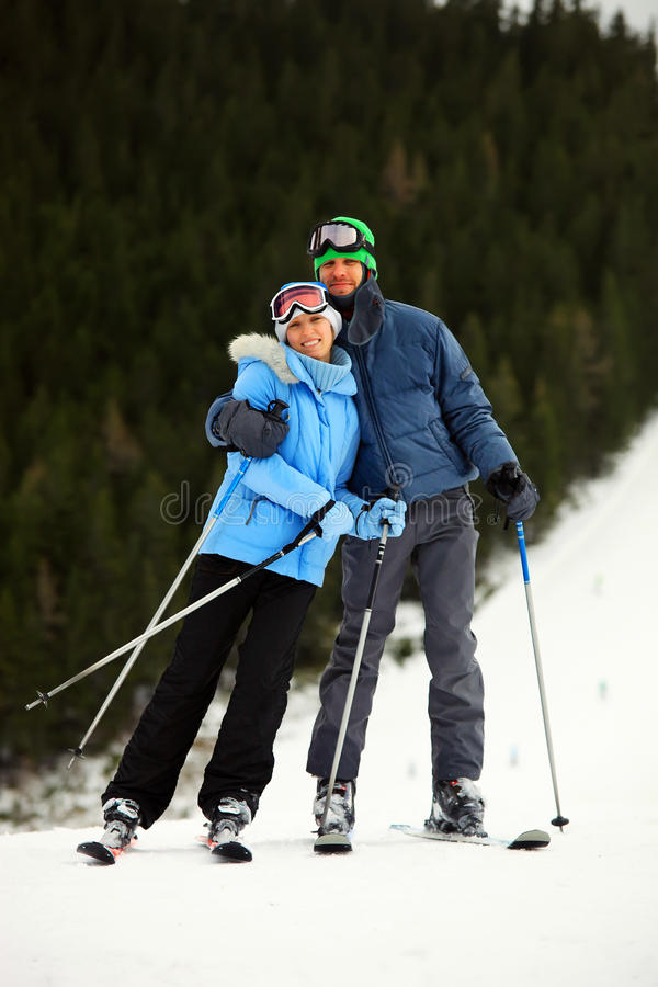 Cheerful young couple on skis stock photo