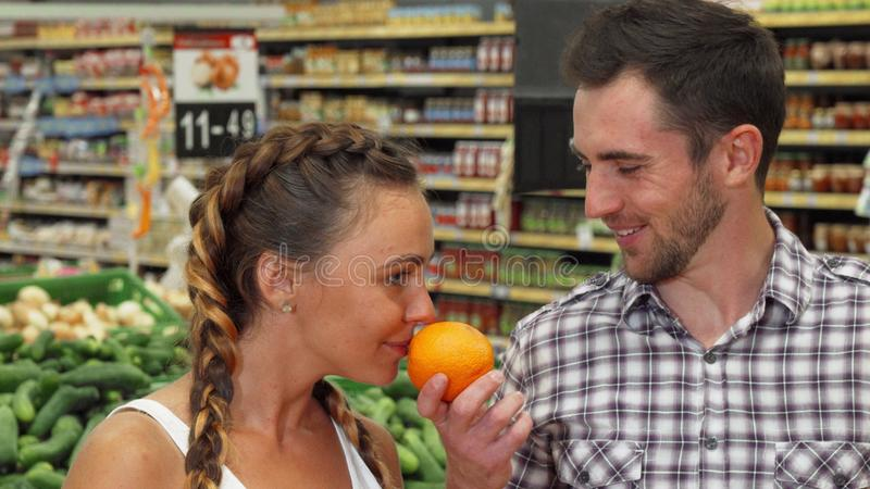 Cheerful young couple smelling oranges while shopping for food. Handsome young men and his beautiful girlfriend smelling oranges, choosing fruits to buy at the stock photo