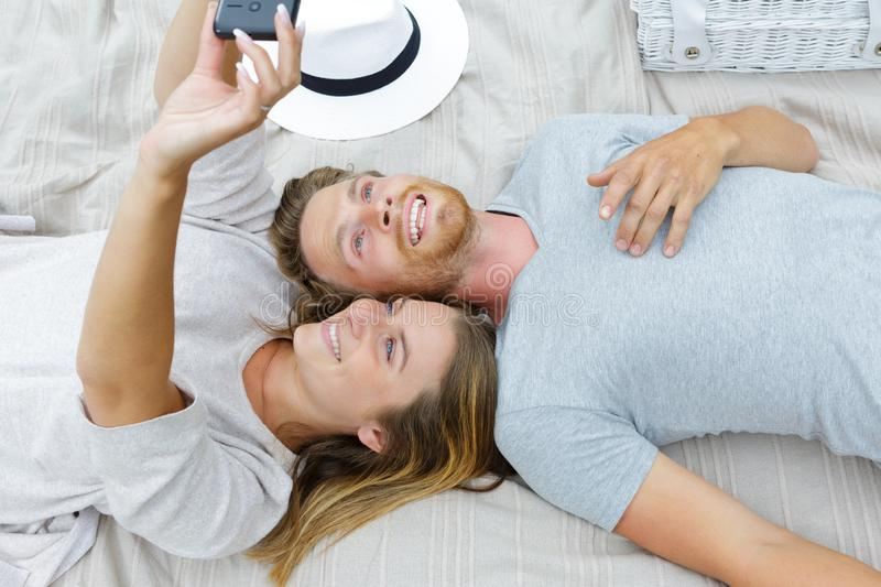 Cheerful young couple taking selfie lying in park stock photos