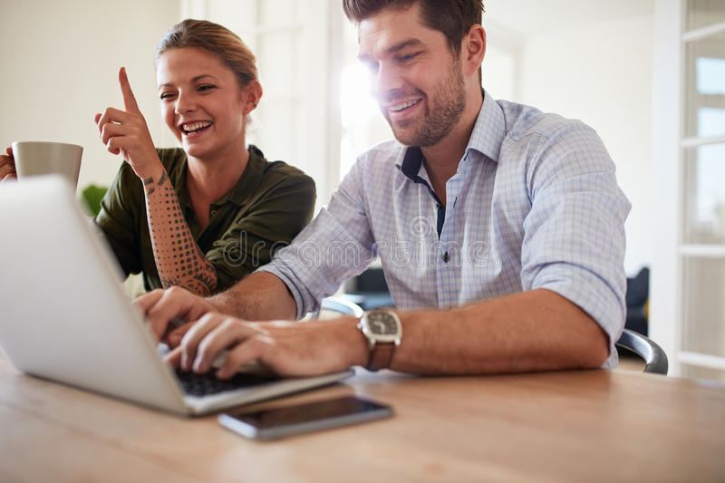 Cheerful young couple using laptop at home stock photos