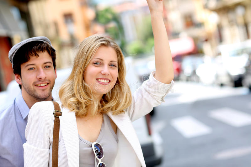 Cheerful young couple waving for taxi in town stock photography