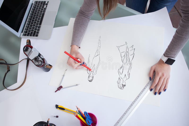 Cheerful young designer is working on her project. Close up of arms of female photo artist drawing sketches in the office. The woman is standing. There are a royalty free stock photography