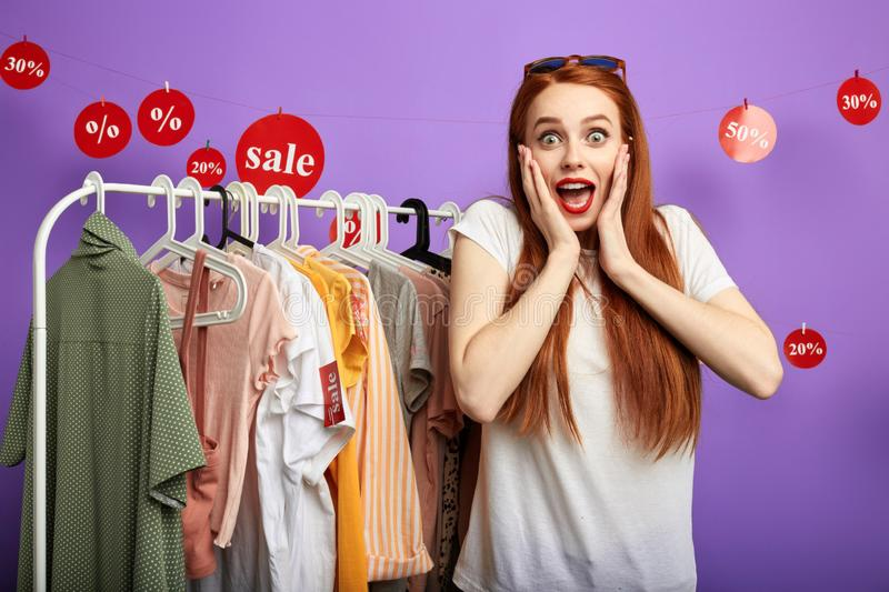 Cheerful young emotional woman inviting people to the shop stock photos