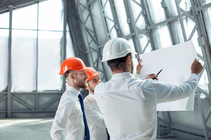 Cheerful young engineers are discussing a new royalty free stock photo