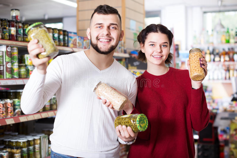 Cheerful young family choosing purchasing canned food for week a stock photography