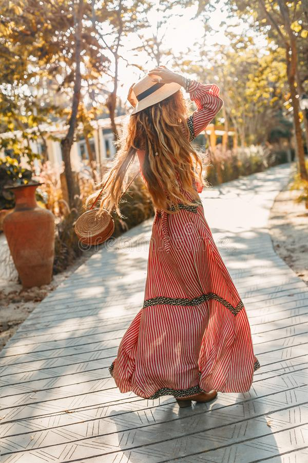 Cheerful young fashionable woman in hat having fun outdoors at sunset stock image