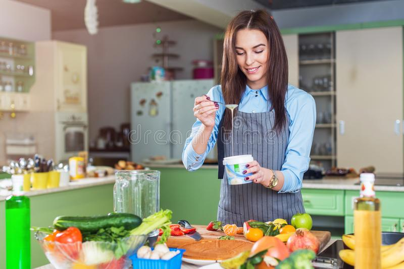 Cheerful young female chef cooking dessert adding condensed milk in dish in her kitchen.  royalty free stock images