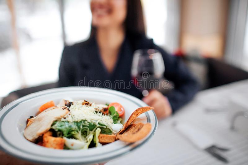 Cheerful young female customer sit at table and smile. She hold glass of red wine. Bowl with salad and meat shown on stock images