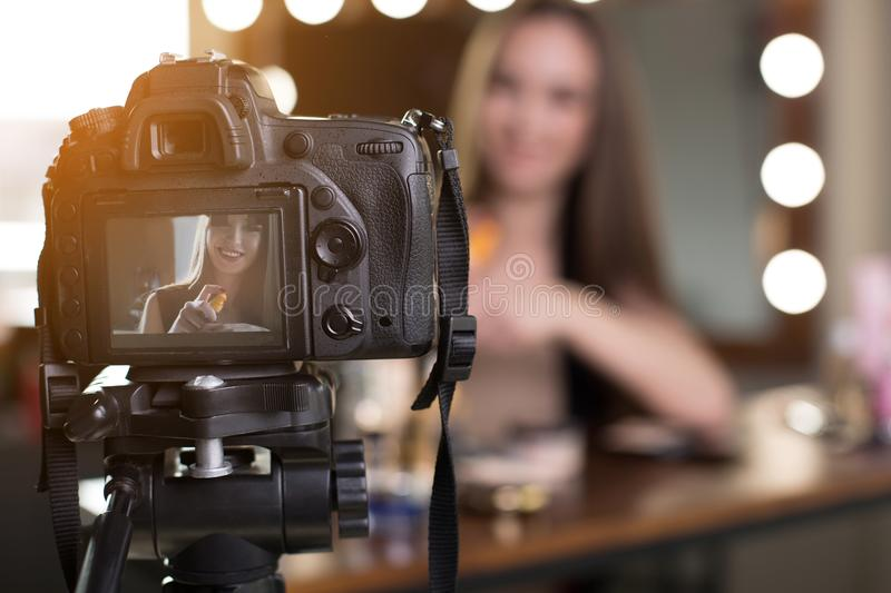 Cheerful young female is filming her beauty blog stock image