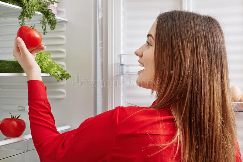 Cheerful young female happy to see tomatoes in fridge, going to make vegetable salad, keeps to diet, stands in front of opened ref. Rigerator. Cute woman royalty free stock image