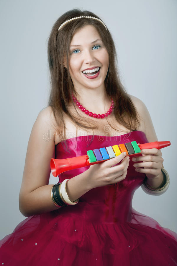 Cheerful young female laughing and holding a toy fife royalty free stock photos