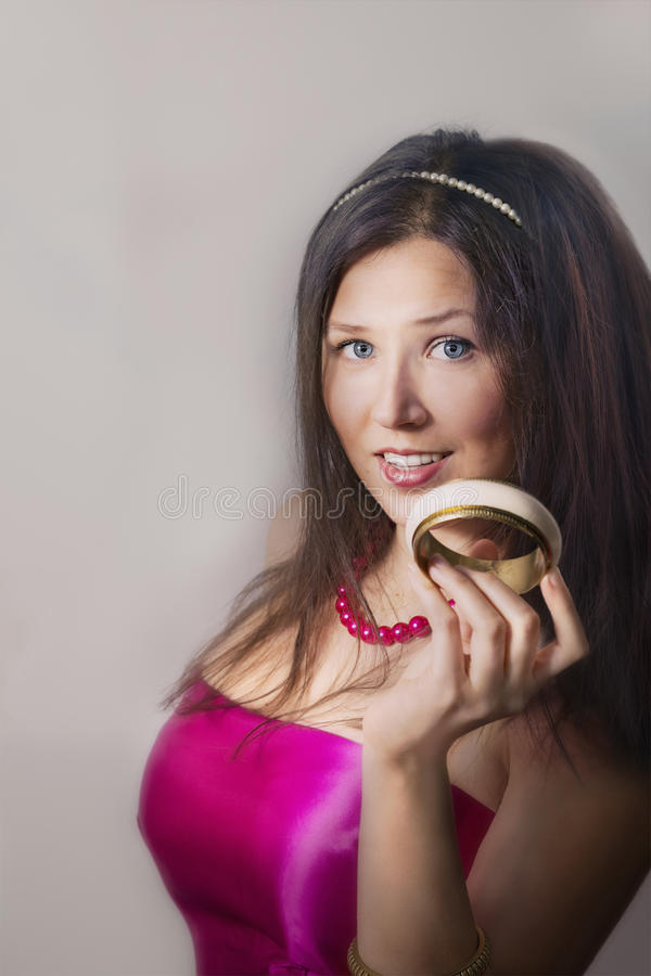 Cheerful young female smiling and holding bracelet royalty free stock photo