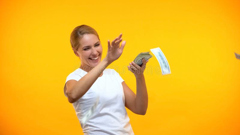 Cheerful young female throwing money around, prosperity excitement, earnings. Stock photo stock photos