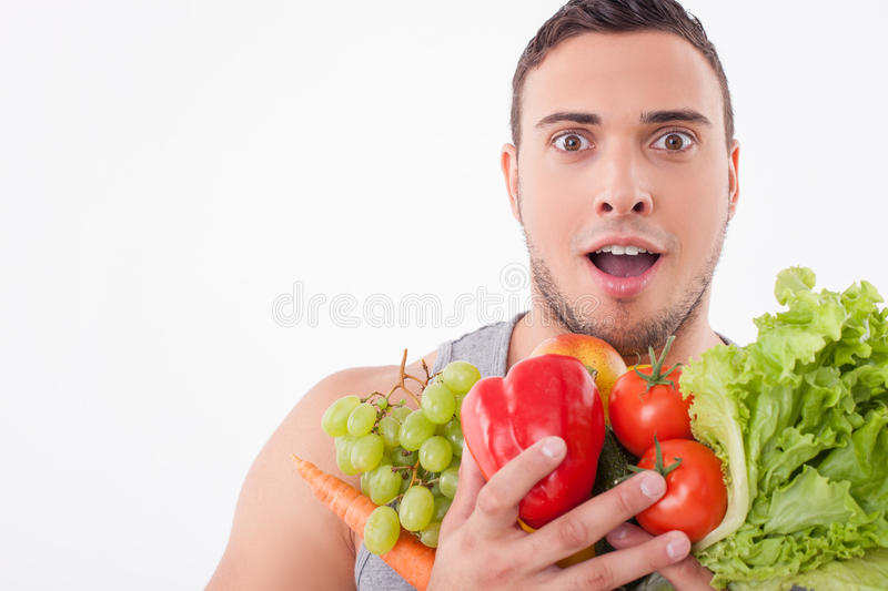 Cheerful young fit man likes healthy food stock photos