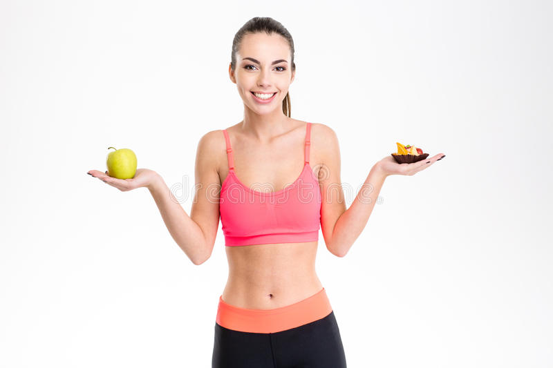 Cheerful young fitness girl holding healthy and unhealthy food stock photo
