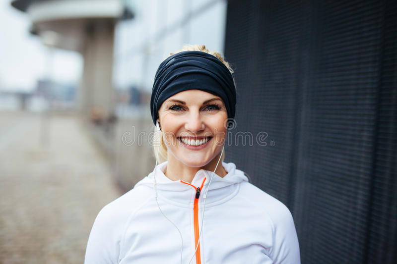 Cheerful young fitness woman. Portrait of cheerful young fitness woman. Smiling young female athlete in sports wear outdoors stock image