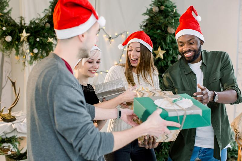 Cheerful young four international people celebrate Christmas and New Year together in cozy decorated studio. Group of royalty free stock photography