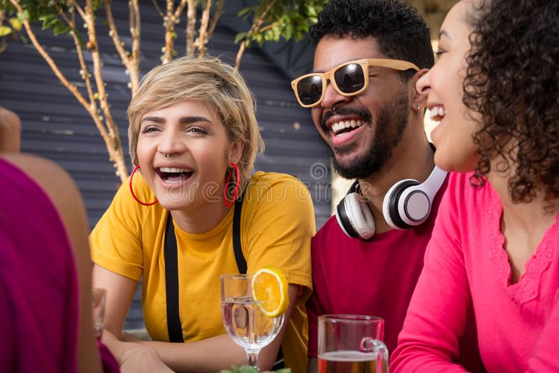 Cheerful young friends cheering and drinking together at cafe bar outdoor. Spring, warm, togetherness, lifestyle, diversity royalty free stock photos