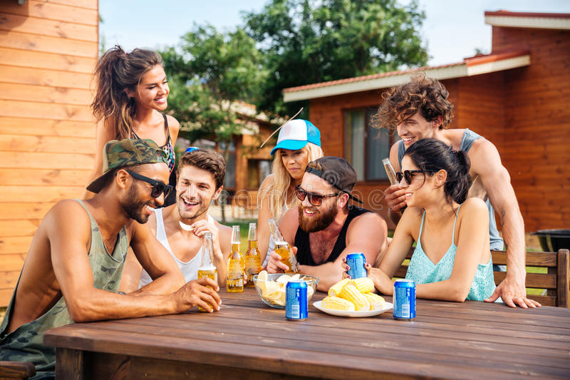 Cheerful young friends drinking beer outdoor summer party royalty free stock photo